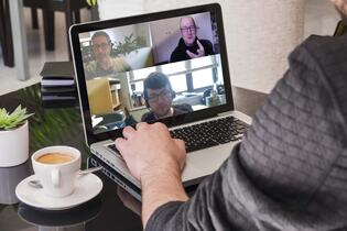 Someone watching a Chalkline webinar on their laptop with a coffee