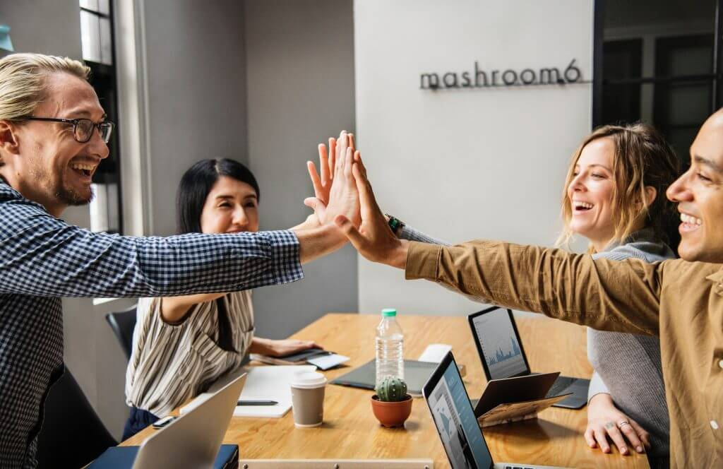A group of colleagues high fiving because of a successful project