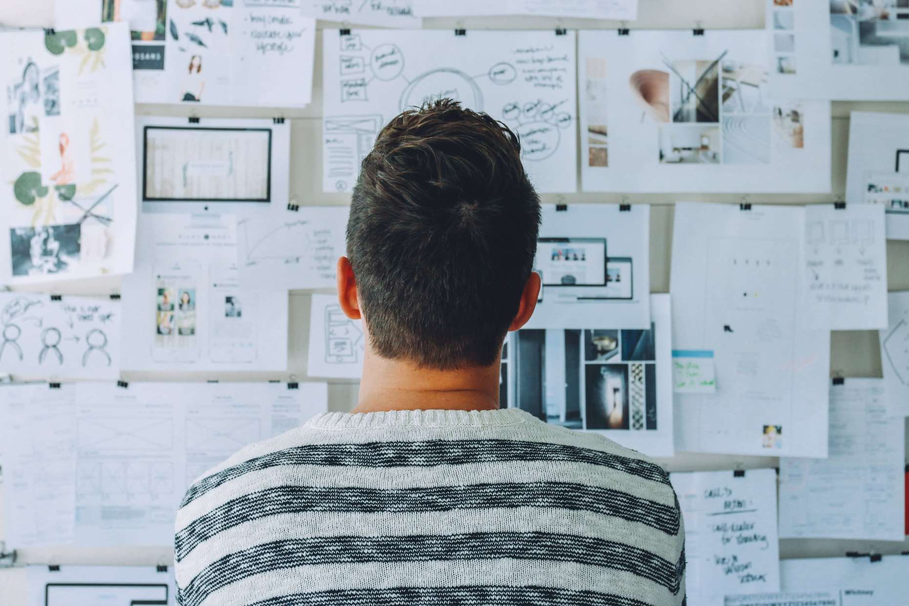 Man looking at a wall full of IT project planning documents