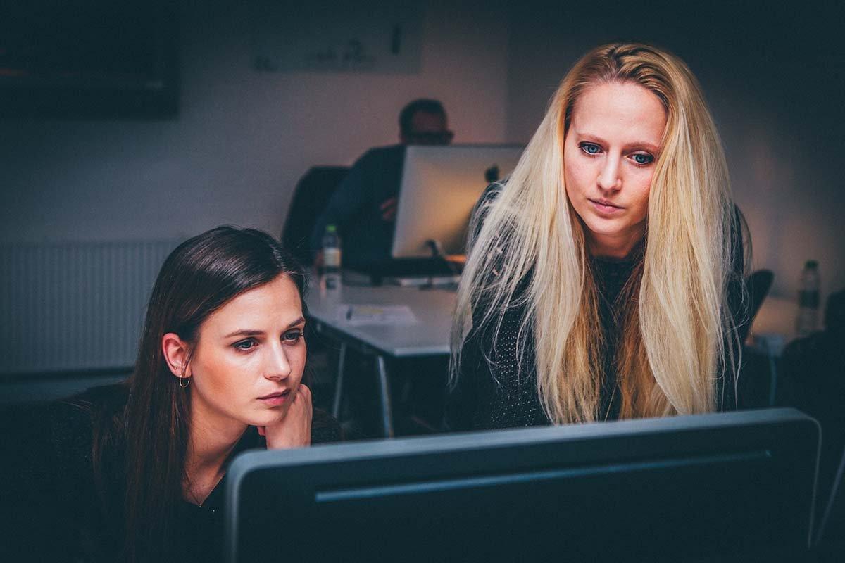 Two women looking at a desktop screen