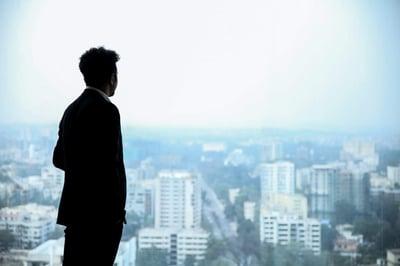 man standing in window overlooking city skyline