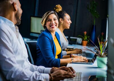 People smiling in an office (How to promote wellbeing in the workplace with Microsoft Viva blog)