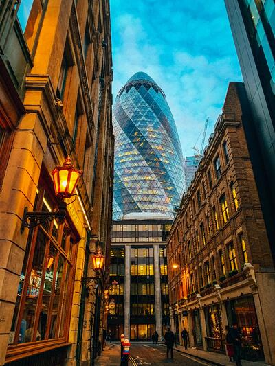 A city of London street with the Gherkin building looming at the end of it.